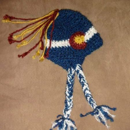 crocheted hat in CO flag colors with ear flaps, thick braids, and top tassel